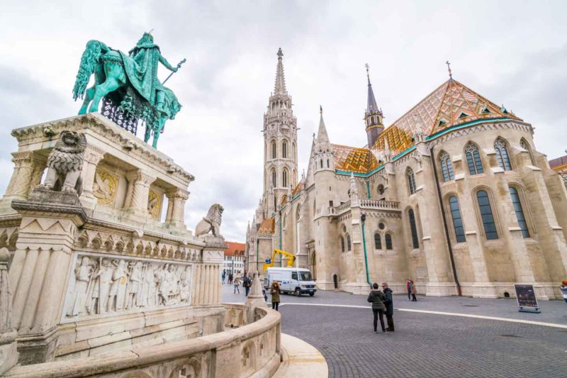 A green copper statue in front of the Matthias Church in Budapest