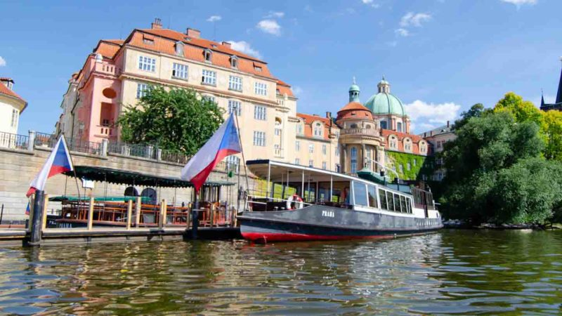 River Boat in the Vltava river in Prague with a Czech flag - Best things to do in Prague