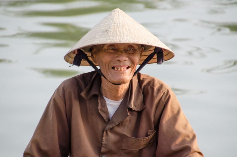 Vietnamese man on a boat in the Mekong Delta with a Vietnamese rice hat