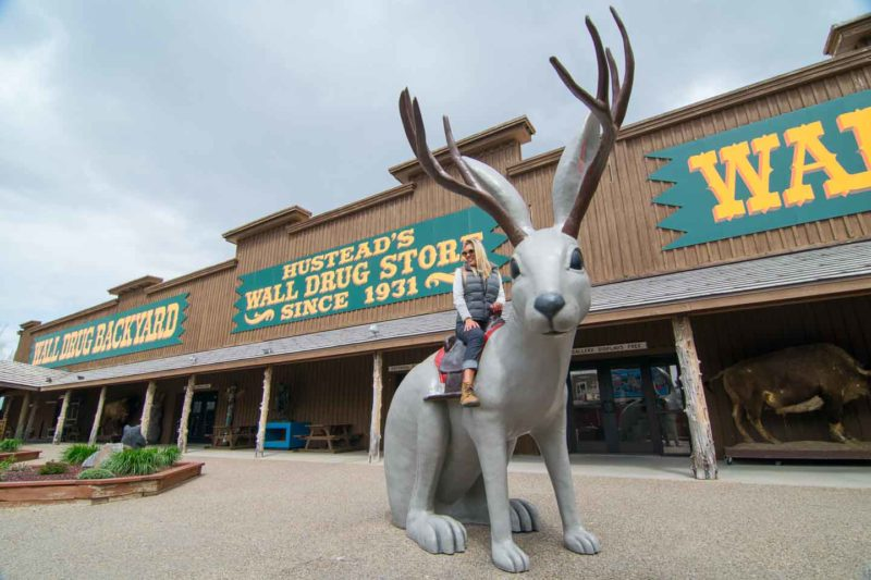 Woman ride large jackalope in the backyard of Wall Drug in Wall South Dakota - A must on any road trip