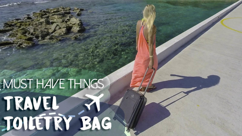 Featured image travel toiletry bag of a woman walking on a long pier with a carry on bag