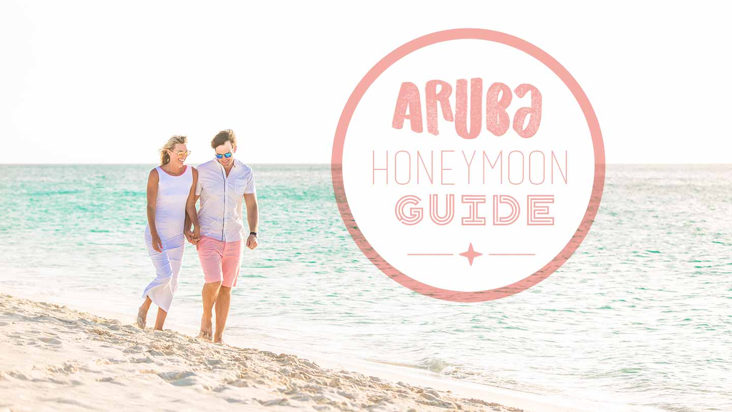 Couple walking the beach in Aruba on a honeymoon -featured image