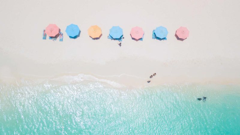 pastel beach umbrellas on Eagle Beach - Aruba Honeymoon