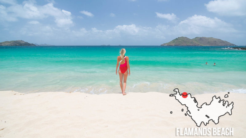 Woman in a red swimsuit stands on Flamands Beach one of the best beaches in St. Barts
