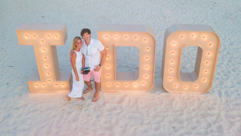 "couple standing in front of an ""I Do"" illuminated statue during the Caribbean's largest vow renewal in Aruba"