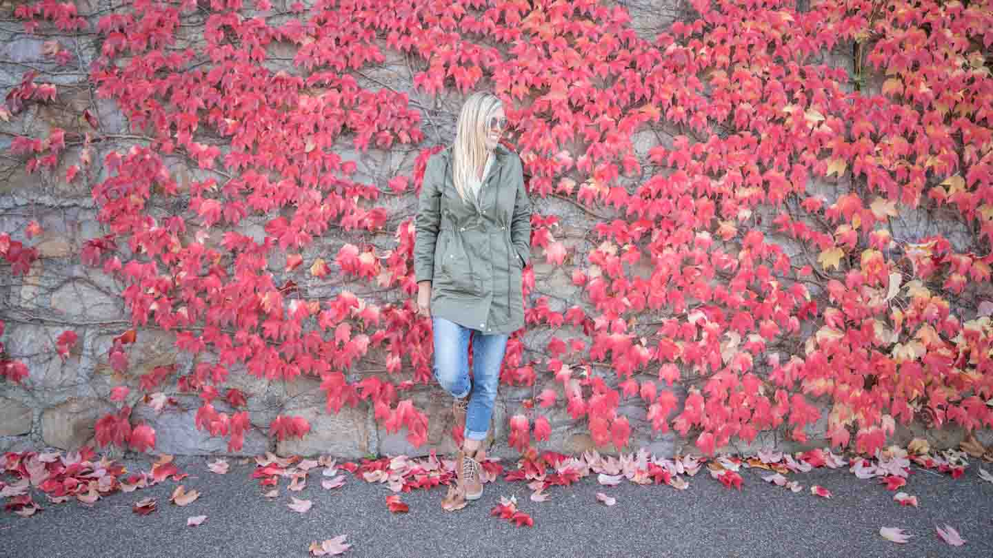 Woman with Merrell Boots from Zappos in front of a wall covered in red leaves