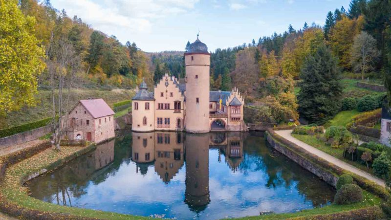 drone photo of Mespelbrunn Castle with pond reflection, one of the best kept secret castles in Germany