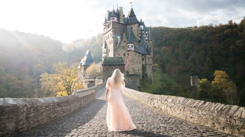 Woman in a dress in front of Burg Eltz Castle in Germany