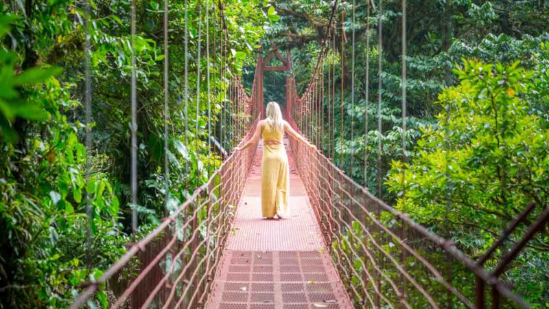 Woman standing on hanging bridge in monteverde reserve - Honeymoon Destinations in Costa Rica