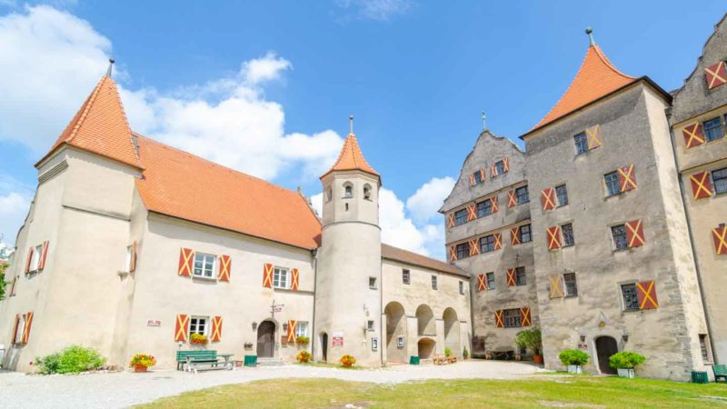 Harburg Castle with light colored stones orange roof and wooden shutters painted orange - top sights along the romantic road in Germany
