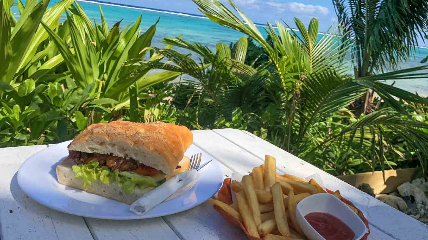 Chicken Sandwich & Chips on a picnic table with the ocean in the background at Charlie's Cafe restaurant in the Cook Islands