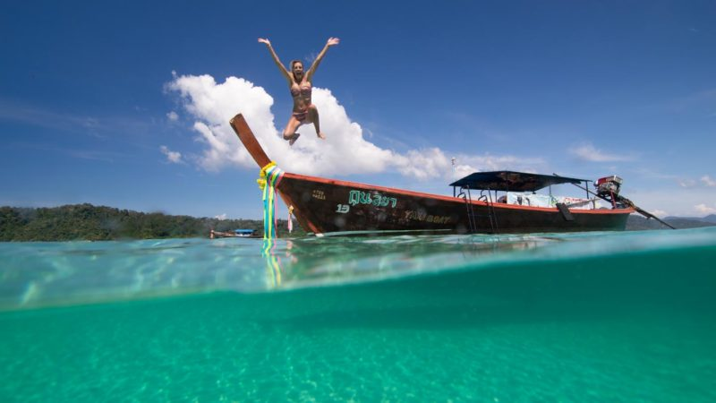 Woman jumping off of a Thai longtail boat in Koh Lipe