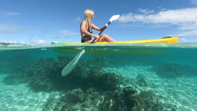 woman paddling a kayak in the Cook Islands - GoPro Filming Tips