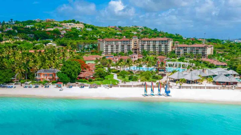 Drone view of Sandals Grande Antigua Resort showing the beach and hotel rooms - Best Sandals Resort