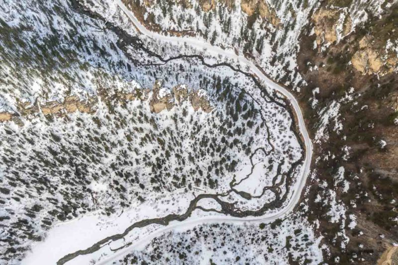 High Aerial Photo of the snowmobile trails in the Black Hills, SD - snow and river bending around rock formations