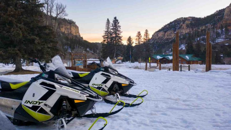 two Polaris Adventures Snowmobiles parked at the Spearfish Canyon Lodge at Sunrise - Orange and Blue skies with white and yellow sled in the foreground