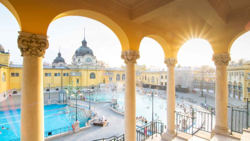 sunburst coming through the yellow archway of the Szechenyi Thermal Baths - Famous Budapest Baths