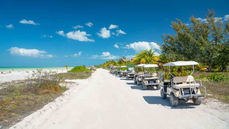 a line of golf carts for rent parked on Holbox island - Things to do in Holbox
