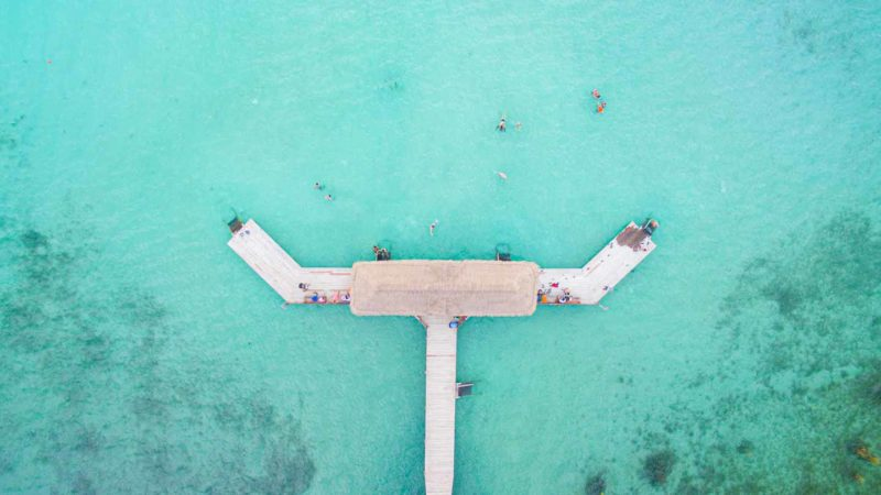 Aerial view of Thatched hut on the end of a dock in Laguna Bacalar Mexico - Aqua colored water and tan palm thatching