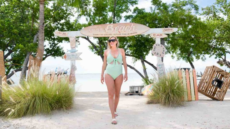 woman standing in front of the MM88 beach sign at mile marker 88 on the overseas highway during a Florida Keys road trip