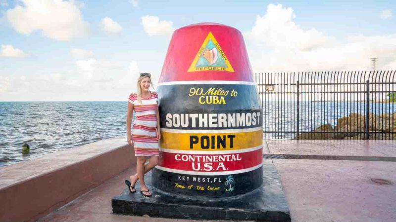 """woman in a striped dress standing next to the """"Southernmost Point"""" Marker Buoy - top tourist attractions while driving to key west florida"""