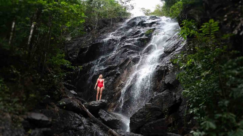Woman in a red swimsuit standing in front of a waterfall in Koh Phangan Thailand
