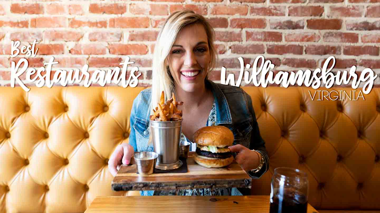 "Woman holding a hamburger for the cover image of ""Best Restaurants in Williamsburg Virginia"" Text overlaid"