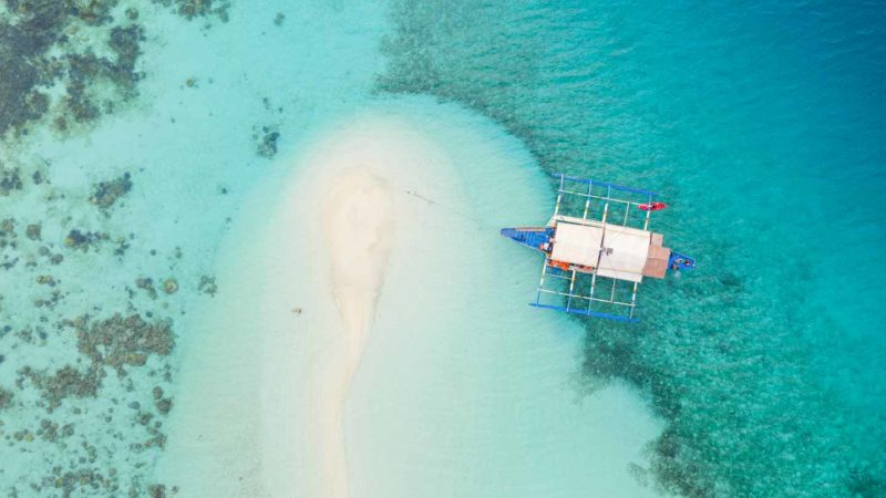 Top Down Drone Photo of Bulog Dos Island - traditional boat in clear water near a sandbar